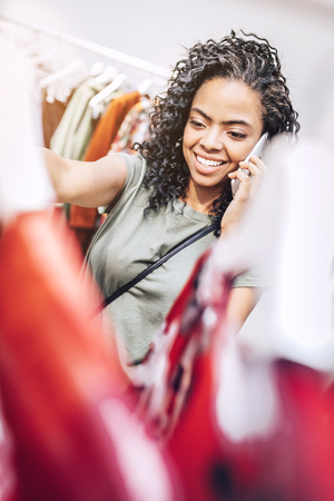 Smiling woman speaking on phone in clothing shop