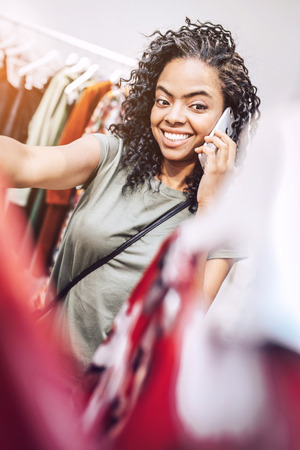 Stylish ethnic woman speaking on phone in shop