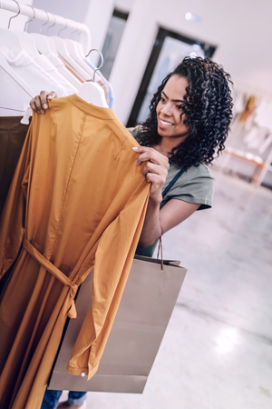 Beautiful woman holding hanger in shop
