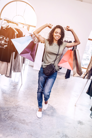 Happy woman carrying paper bags in store