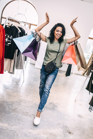 Happy bright woman in shop with bags