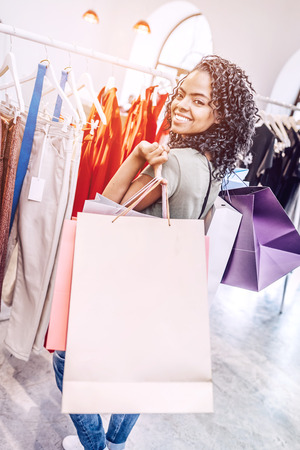 Charming woman with colorful shopping bags