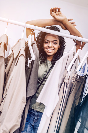 Smiling black woman behind rack with clothes Stock Photo