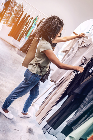 Side view of casual black woman choosing trendy clothes on hangers in shop Stock Photo