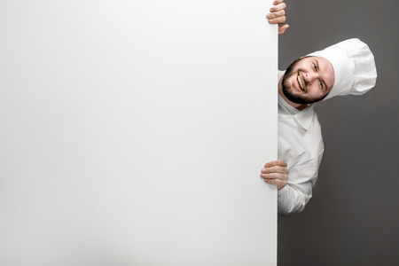 Cheerful chef emerging from behind whiteboard