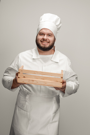 Smiling chef with wooden box