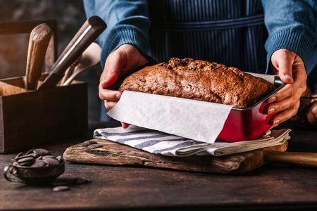 Woman serving grain loaf of bread Reklamní fotografie