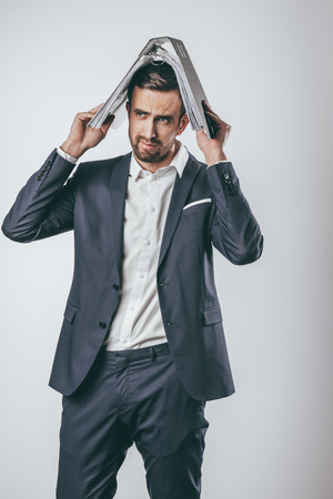 Serious businessman holding folder on head