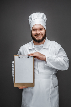 Cheerful chef showing empty clipboard