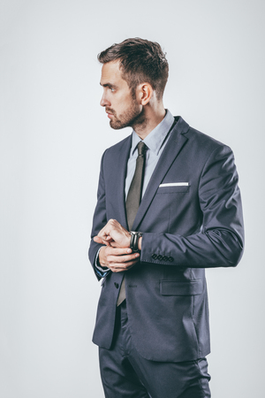 Serious businessman touching wristwatch and looking away