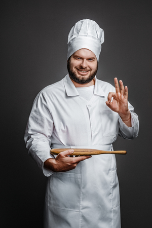 Smiling chef with empty board showing OK gesture