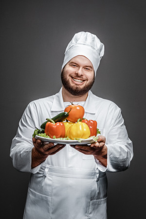 Smiling chef showing plate with vegetables