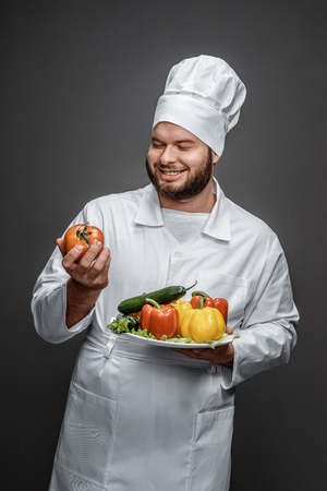 Chef with vegetables looking at tomato