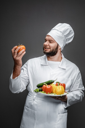 Funny chef with vegetables looking at tomato Stock fotó