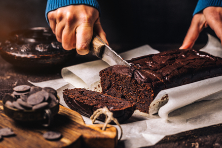 Faceless view of woman at table cutting into slices sweet chocolate bread cake on parchment paper at table Stock fotó