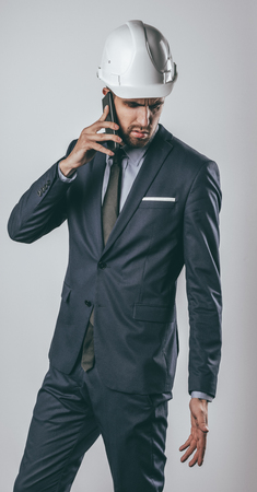 Attractive male in white helmet and stylish suit frowning and looking down during smartphone conversation on light gray background Stock fotó
