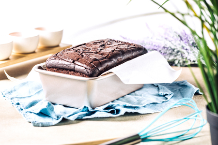 Arrangement of metal form with homemade baked chocolate bread cake on blue napkin on table with flowers Stock fotó