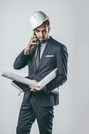 Attractive tired man in suit and helmet holding blueprints and notebook and talking on smartphone while standing on light gray background Stock fotó