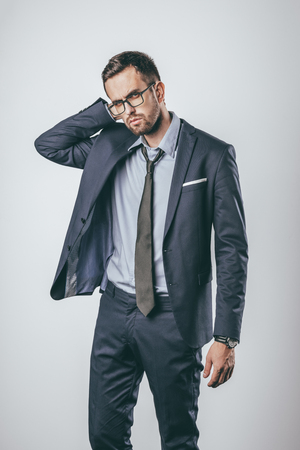 Handsome male in stylish suit touching head and looking at camera with serious face expression while standing on light gray background Stock fotó