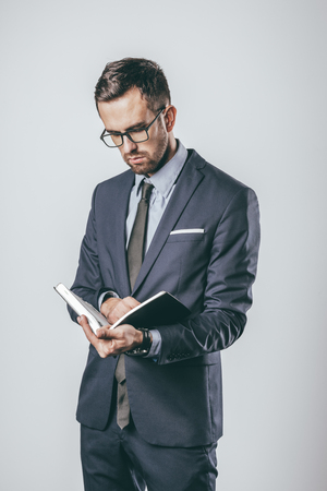 Serious businessman reading notebook