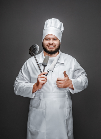 Cheerful chef recommending utensils Stock fotó