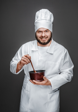 Smiling chef stirring food in saucepan