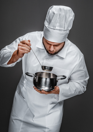 Chef with ladle looking inside saucepan