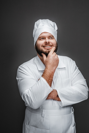 Thoughtful bearded chef looking up