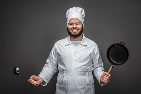 Cheerful cook with ladle and frying pan Stock fotó