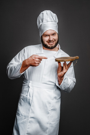 Cheerful chef pointing at empty board