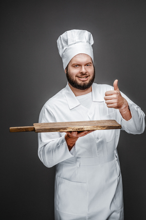 Confident chef with board gesturing thumb up Stock fotó