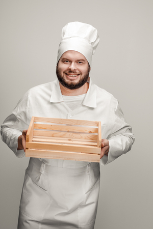 Smiling chef showing empty lumber box Stock fotó