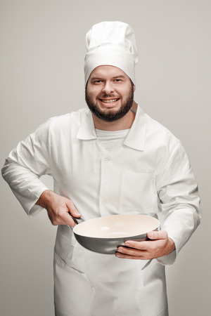 Smiling cook with modern skillet Stock fotó