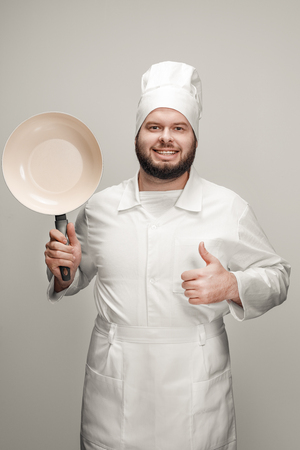Smiling chef recommending modern skillet