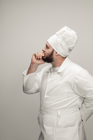 Thoughtful overweight chef looking away
