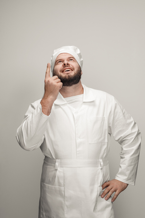 Cheerful overweight chef pointing up
