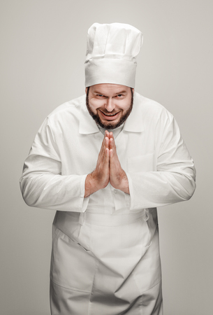 Cheerful chef clasping hands in gratitude