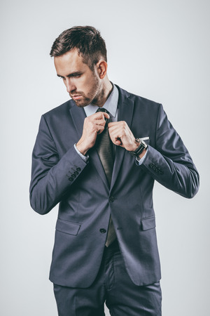 Businessman adjusting tie and looking town Stock fotó