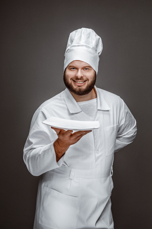 Smiling chef presenting empty plate Stock fotó