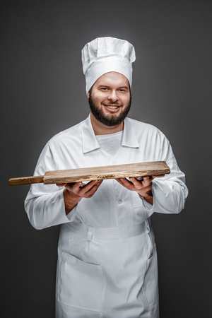 Smiling chef presenting empty board