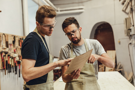 Serious carpenter showing papers to colleague