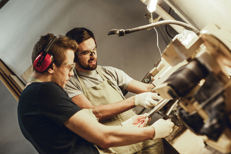 Smiling man using joinery equipment with colleague