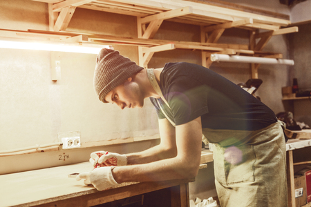 Young guy making marks on wood in joinery Stock fotó