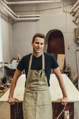 Handsome young guy in apron smiling and looking at camera while leaning on table in workshop