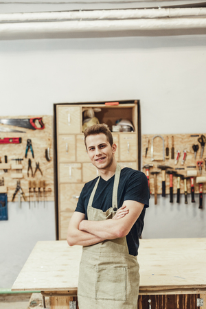 Attractive young guy in apron smiling and keeping arms crossed while standing near table in workshop and looking at camera Stock Photo