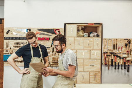 Bearded man in apron smiling and demonstrating documents to young colleague while standing in modern joinery together Stok Fotoğraf - 115947801