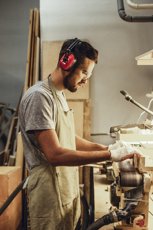 Side view of handsome craftsman in earmuffs and goggles standing near workbench and using professional belt sander