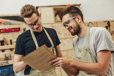 Two handsome young men in safety goggles cheerfully smiling and reading papers while working in joinery together Imagens - 115947814