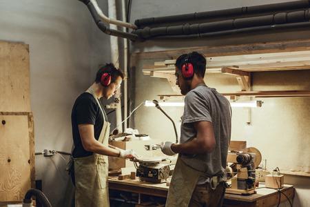 Carpenters in earmuffs standing near workbench
