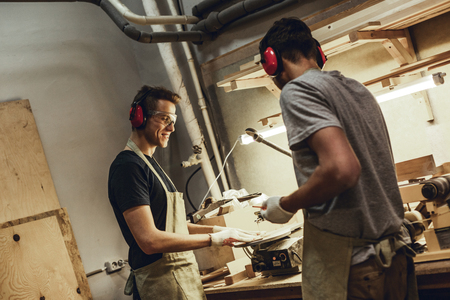 Smiling carpenter using jigsaw with colleague Stock fotó - 115949860